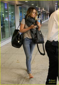 light denim skinny jeans, neutral comfy tee shirt, gray scarf, black bag   the perfect travel outfit