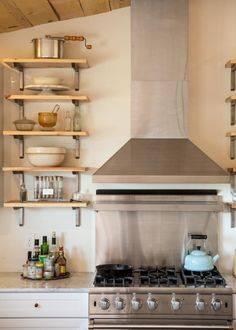 A sleek stainless steel range hood adds contemporary flair to this cottage-style kitchen. Open shelving allows for handy access to kitchen essentials and also creates a delightful display.