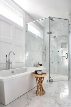 This master bathroom was renovated to include a large, curbless shower in the corner, a freestanding air tub and custom paneled walls. High quality porcelain tiles add a realistic Carrara marble look.