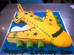 3D Airplane shaped cake iced in yellow butter icing decorated with green stars | by Charly's Bakery