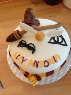 Harry potter cake with broomstick, golden snitch, sorting hat, Harry's glasses and deathly hallows symbol.