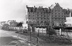 This photo circa 1944, Worthing, West Sussex, England. Building began in 1900 on what was to have been The Hotel Metropole, at the end of Grand Avenue along the seafront. With nearly 1000 rooms it was designed to attract the aristocracy and wealthy Edwardians. Delays over several years lead to financial difficulties which caused all building to cease. The structure was left unfinished until turned into Flats in 1924. The building is now known as Dolphin Lodge.