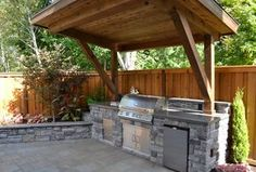 Rustic Patio with Polished concrete, Outdoor kitchen, Raised beds, Stacked stone, Fence, exterior stone floors