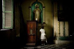 A woman, who practices Santería prays at the Cathedral of Santiago de Cuba by Tomas Munita