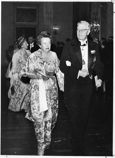 "Maria Goeppert-Mayer (1906-1972), walking in to the Nobel ceremony with King Gustaf Adolf    Description: This photo was taken in 1963, as physicist Maria Goeppert-Mayer (1906-1972) was being escorted by King Gustav Adolf of Sweden to a gala banquet following the ceremony during which she received the Nobel Prize in physics for development of the model of atomic nuclei in which the orbits of protons and neutrons are arranged in concentric ""shells"""
