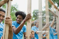 Group Of Volunteers Holding Wooden Frame At Park Stock Photo 168359133
