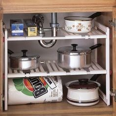 """Under-Sink Shelf turns wasted space into storage! Sliding slats fit around pipes. Kitchen under-sink plastic frame extends 18"""" - 28"""" wide; 12"""" deep, 16"""" high. Assemble easily. Unclutter overcrowded cabinets!"""
