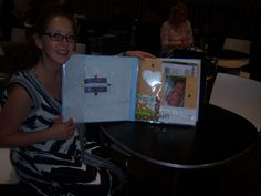 Lindsay posing next to the scrapbook I created for her son's first year.