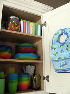 Kids Cupboard ~ I did something similar to this but on a much, much smaller scale. I have a container that has my grand-daughter's dinnerware. a couple plates, a couple sippy cups, and a container that holds her utensils. I'm not sure if I'm going to do the bib thing or not.