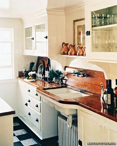 A nice layout for a small kitchen.  Wooden counter tops add an element of warmth to the space