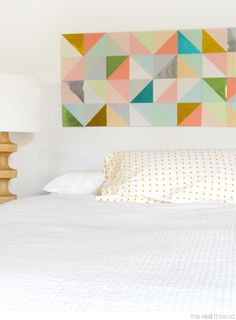 Geo paper patchwork headboard made from origami papers on foam board—stick up with poster putty or removable tape. #homefakeovers