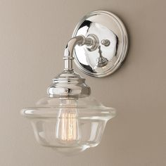 "Timeless Schoolhouse Sconce Timeless schoolhouse style meets todays design with a contemporary twist on an instant classic. Clear glass and polished chrome add even more timeless appeal. Available in sconce, 2 light bath light and 3 light bath light. (12.75""Hx8""W)"