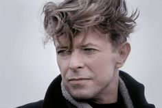 """Robert G. Zuckerman took his beautiful, touching photograph of David Bowie in December 1990, Coney Island, NY. """"One of my first still jobs on a film set, covering the final New York portion of the indie production The Linguini Incident. This portrait of David Bowie was made on a cold, grey, blustery December morning as he stood on the beach, in between cigarettes."""""""