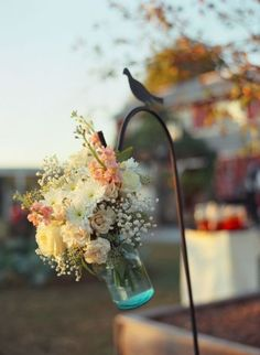 Great way to great guests by using a row of garden stakes to hang mason jars filled with flowers. For The Love of Jars! Decorating with Jars Collection
