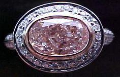Bezel set fancy color (pink) oval in two-tone bezel. Bead set diamonds in halo and in shank.