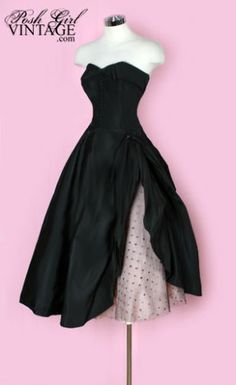 1950s Pink and Black Cadillac Party Dress.  Made of black medium weight taffeta, skirt is lined in pink rayon acetate with a layer of pink tulle and another layer of black polka dot tulle on top that peaks out the side. The skirt is gathered and lifted on one side with a black decorative button sewn on to show the tulle underneath.