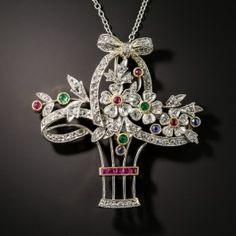 A beautiful bouquet of gem-centered rose-cut diamond-petaled flowers are artfully arranged in a matching vase, all expertly hand fabricated in platinum and tied up with a bow in this exquisite Edwardian era treasure. The removable pin-stem allows it to be worn either as a brooch or pendant. Circa 1915. The newer platinum chain measures 18 inches. 1 3/8 by 1 1/4 inches.