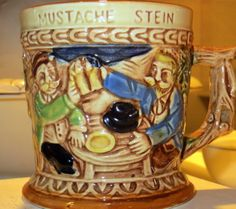 Mustache Stein, c. 1970s Made in Japan  Ceramic  Mustache steins such as these were made to keep a man's mustache clean and dry. The bar that extends across the top of the mug has a small opening to allow liquids to pass through, but is large enough to protect the mustache from steam and foam. Serving as a novelty item for collectors, this mug is a modern replica of what once existed.   http://www.morrismuseum.org/