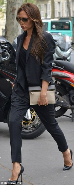 Victoria Beckham looked chic in her all-black outfit of a trouser suit and heels... complete with zipped clutch.