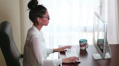 Young businesswoman working on her computer in the office. Writing an email clicking the keyboard and mouse. A clerk emailing a corporate letter and chatting. Stock Video Footage - VideoBlocks
