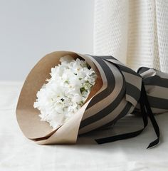 Simple white flowers wrapped in striped paper is so pretty.