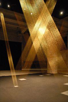 """Ttéia I, C, 2002 Installation de Lygia Pape Brésil (1927-2004) Cette oeuvre diaphane constitue une très subtile entrée en matière dans l'exposition de l'Arsenal, par son traitement de la lumière, portée jusqu'au sol par des fils d'or très fins, qui rayonnent dans l'obscurité comme le soleil pourrait le faire à travers des trous dans la charpente. Exposition de l'Arsenal (Arsenale) """"Making Worlds"""", """"Fare Mondi"""" 53 ème Biennale de Venise www.labiennale.org/en/art/exhibition/53rd.html"""