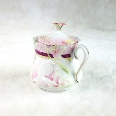 A rare, beautiful collectors porcelain piece. RS Prussia porcelain Hidden Figures, hidden image, small sugar bowl. An unmarked, antique porcelain sugar bowl. Romantic white porcelain with highlights of pink, decorated with flowers, burgundy and gold striping, and the hidden profile of a woman. A gorgeous Art Nouveau small sugar bowl with lid. The ruffled edge and single handle have been highlighted in gold. One petal from the lovely handle of the lid was broken off. The only markings are a…