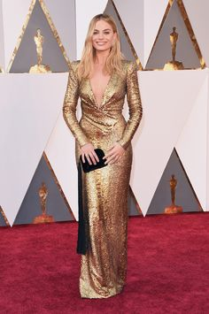 Margot Robbie.. Tom Ford gown and heels; The Row Tassel Wristlet clutch, and Forevermark by Rahaminov Inside Out Diamond Hoop Earrings..