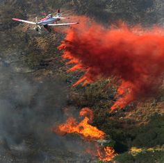 (Steve Griffin/The Salt Lake Tribune) A plane drops its payload of fire retardant on a fire that burns in the mountains near Alpine, Utah Tuesday July 3, 2012.