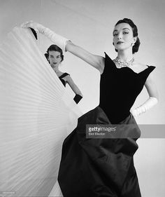 Portrait of two unidentified fashion models, both in sleeveless dresses and elbow gloves, as they pose against a white background, New York, New York, October 1950. The clothing was designed by Winnie award-winning designer Charles James.