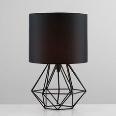 A striking table lamp, ideal in modern home. Design features drum shade in geometric base. Ideal as bedside lamp. Bedside Lighting, Bedside Table Lamps, Bedroom Lamps, Home Lighting, Bedside Lamps Industrial, Rustic Lamps, Black Table Lamps, Black Lamps, Bedside Lamps Black
