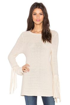Natural ivory, semi-sheer sweater featuring a scoop neck and exaggerated long fringed, slight bell sleeves. The elongated bodice works perfect with skinny jeans or leggings!    50% Polyester, 50% Cotton Dry clean or hand wash cold A uniquely designed, light-weight sweater that will transition perfectly into spring!