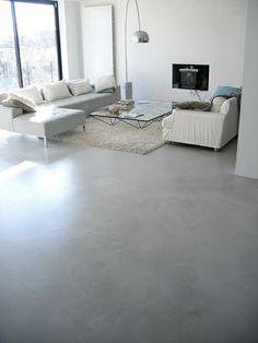 salon avec sol en béton ciré gris et tapis blanc