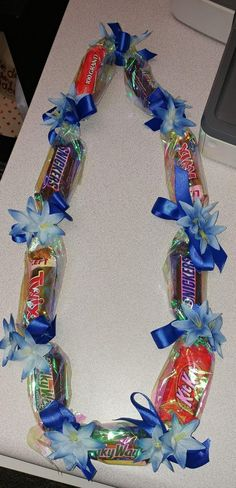 Candy lei Can be customized in Snack size candy Color of ribbon and flowers Wrap (shown with clear wrapping) Flowers/no flowers Diy Graduation Necklaces, Graduation Leis, Candy Necklaces, Candy Wreath, Candy Leis, Candy Lays For Graduation, Grad Gifts, Diy Gifts, Candy Boquets