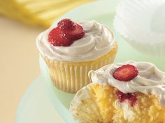 Strawberry Cream Cheese Cupcakes  1  box Betty Crocker® SuperMoist® yellow cake mix  2/3  cup water  1/2  cup sour cream  1/3  cup vegetable oil  2  eggs  3  tablespoons strawberry preserves  1  package (3 oz) cream cheese, cut into 24 pieces  1  container Betty Crocker® Rich & Creamy cream cheese frosting  Sliced fresh small strawberries, if desired