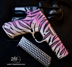 Pink Tiger Colt 1911 with jeweled barrel and magazine. FAB Defense WG1911 grips with magwell funnel. Meprolight night sights and black accents. Shown with black leather Front Line Special IWB holster.