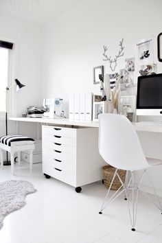 white home office with eames chair, white desk, white rolling chest of drawers with black accents in the form of pictures frames and a strip...