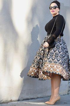Girl With Curves blogger Tanesha Awasthi wears an ankara print full midi skirt and bell sleeve sweater.