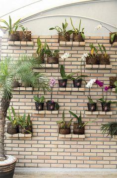 """Na varanda do apartamento, o jardim vertical é composto de lajotas palha. """"Busquei contraste com as cores das plantas que apoiaria nas prateleiras, cada uma formada por quatro tijolinhos"""", conta a designer de interiores paulista Cecilia Cruz. Cortadas ao meio, as peças para revestimento, ficaram com 5,5 cm de espessura e deixam ver o rejunte frisado."""