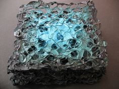 """Abalone book by Jennifer Cartright. This book-form sculpture contains eight """"pages"""" of crocheted wire covered in hand-made paper and acrylic. The pages are sewn end-to-end to create an accordion-style book (shown here in collapsed form). Dimensions: 5"""" x 5"""" x 1"""""""