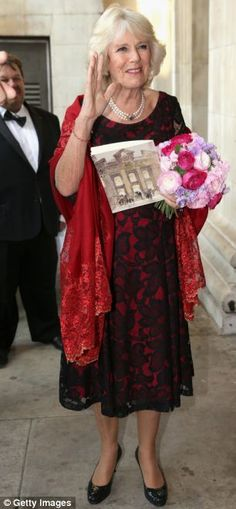 Camilla arrives at the event wearing a red lace shawl and elegant pearls before being handed flowers