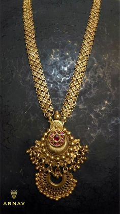 Modern long Haaram with dual pendants and chain pattern in new age design of netted pattern having 3layer flower design all over the chain. The dual pendants are in chandivali shape in increased size and having small gold balls hangings and barmese rubies studded in flower at the centre of the pendant. 12 December 2017
