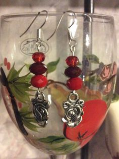 Silver tone metal love rose dangle earrings with red crystal beads. by Createdtreasures23