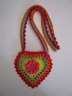 Crochet granny square heart. Can be made into anything, such as this purse. Free crochet pattern.