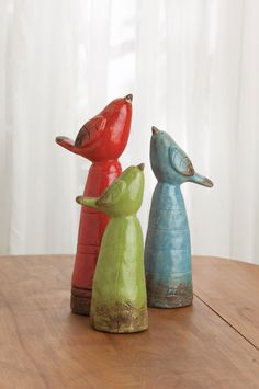 """Three Ceramic Birds Perched on pedestals, beaks pointed skyward—what do they see? Cute and colorful, these little birds exist to make you smile. Rustic glazed ceramic with rubber feet, tallest is 13"""". Set of three as shown: red, green, and blue."""