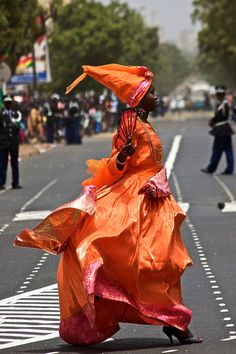 A Senegalese woman crosses the street in her brightly coloured gown #blackfashion