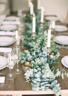 Eucalyptus runner and simple white candle sticks for Christmas dinner table.
