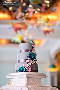 Purple wedding cake with ribbon tiers and decorative floral #Disney