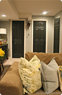 Thrifty Decor Chick:  Nice look for basement. Light grey walls, white ceiling with lots of pot lights and black interior doors