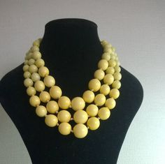 This three strand graduated plastic bead necklace is in two shades of yellow. by ThePemburyEmporium on Etsy
